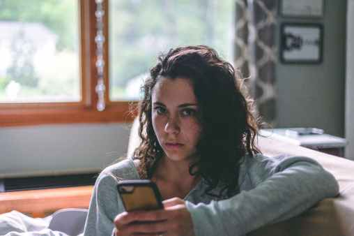 woman holding phone sitting on sofa
